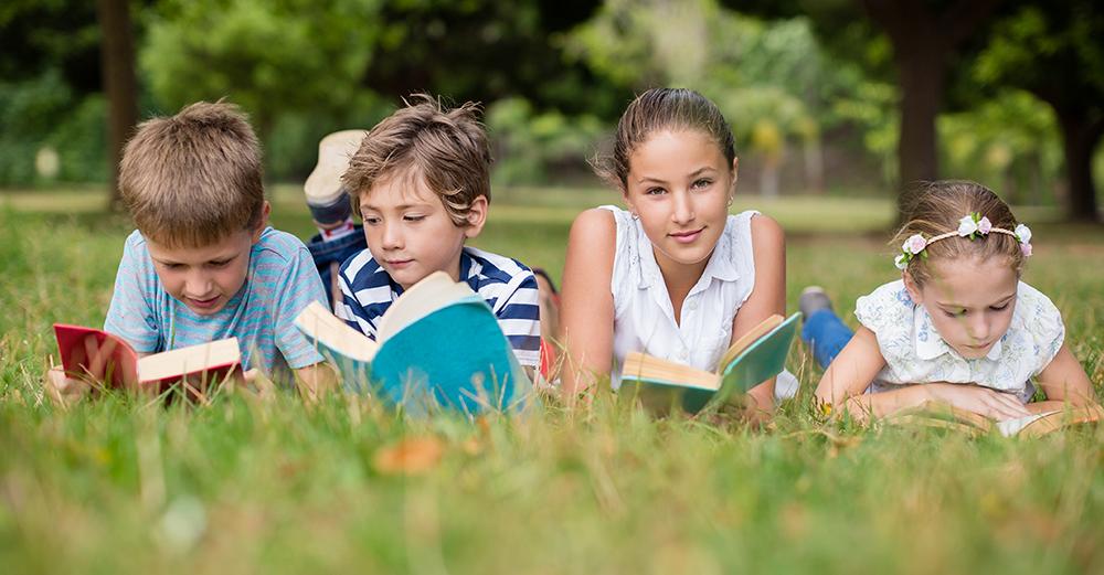 Grup de nens llegint sobre l'herba